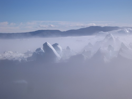 Icebergs floating on a bed of fog.