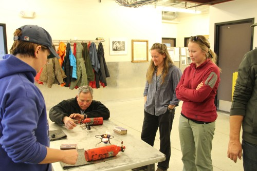 In field safety training, Jess and Ashley supervise stove lighting.